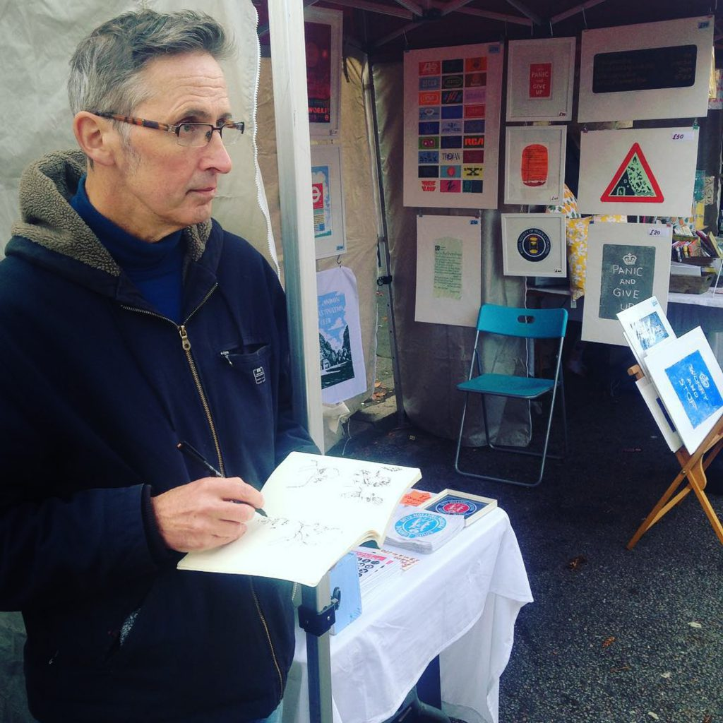 Local artist Martin Grover with his sketch book at Artisans' Market